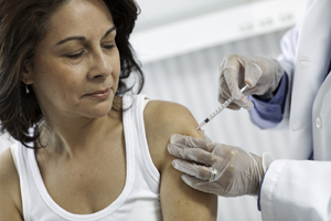 Healthcare provider giving injection in woman's upper arm.