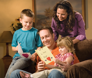 Family, children and wife gathered around Dad, reading handmade greeting card to Dad.