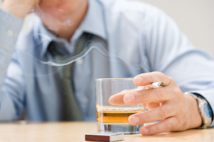 Man smoking cigarette and holding class of whiskey.