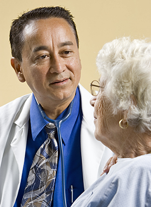 Healthcare provider talking to elderly woman in exam room