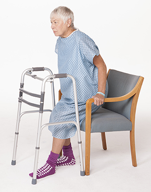 Woman in hospital gown sitting down in chair with walker in front of her.