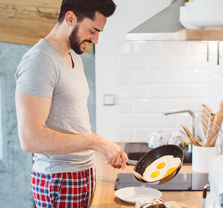 Man in sleeping clothes, about to put cooked eggs on a plate