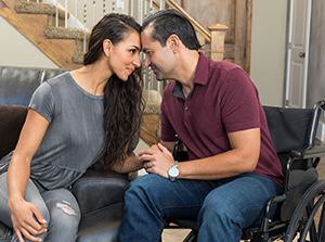 Man embracing with woman in wheelchair.