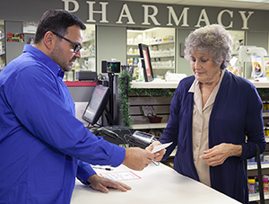 Pharmacist talking with woman about pills.