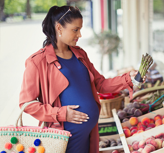 Pregnant woman looking at asparagus at an outdoor market