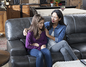 Woman and girl on couch, girl looking unwell.