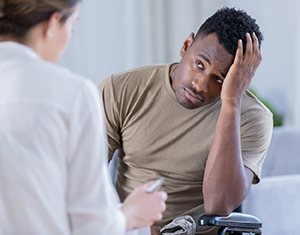 Health care provider talking to depressed male in doctor's office.