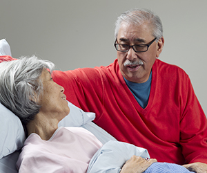 Woman lying in bed. Man sitting next to bed.