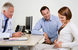 Woman and man sitting at desk with healthcare provider