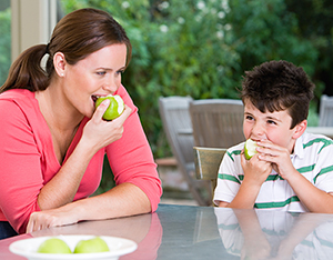 Mother and son eating apples.