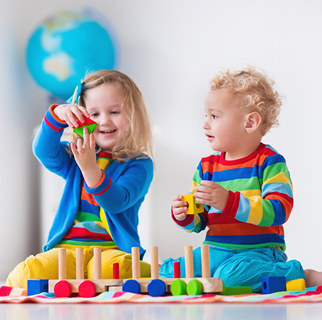 Two toddlers playing with blocks on the floor.