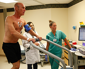 Healthcare providers giving man on treadmill a cardiac stress test.